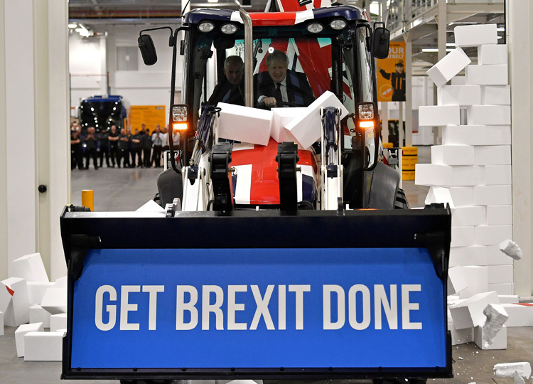 "Britain's Prime Minister and Conservative leader Boris Johnson drives a ""Get Brexit Done"" digger through a fake wall emblazoned with the word ""GRIDLOCK"" during a general election campaign event in Uttoxeter, Britain, on Dec. 10."