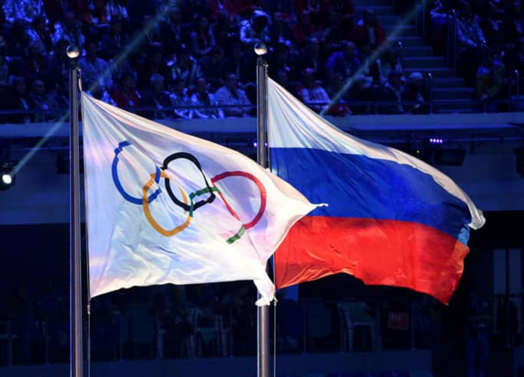 The Olympic flag flies next to the Russian flag during the closing ceremony of the Sochi Winter Olympics on Feb. 23, 2014.