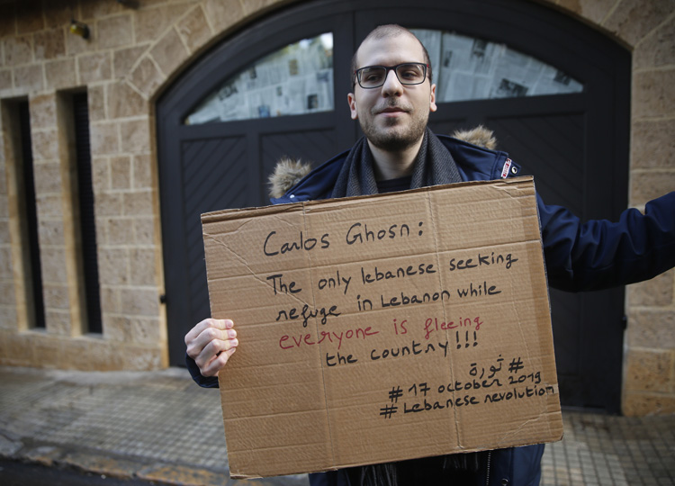 A man poses with a placard outside ex-Nissan chief Carlos Ghosn's house in Beirut on Jan. 5. Ghosn jumped bail in Japan and fled to Lebanon in a dramatic escape.
