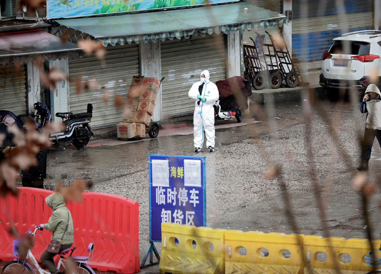 A worker in a protective suit is seen at the closed seafood market in Wuhan, Hubei province, on Jan. 10. The seafood market is linked to the outbreak of the pneumonia.
