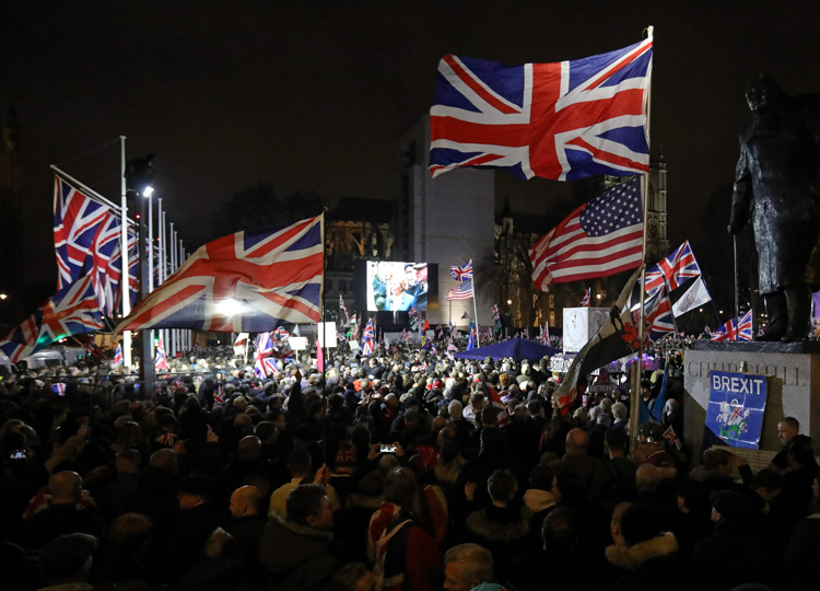 Brexit supporters wave flags as they wait for the festivities to begin in Parliament Square, the venue for the Leave Means Leave Brexit Celebration in central London on Jan. 31.