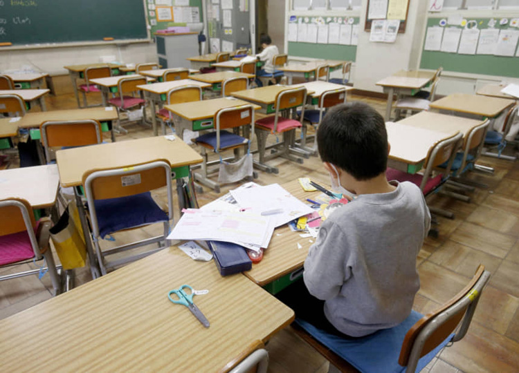Two students study in an almost empty elementary school classroom in the city of Saitama on March 2.