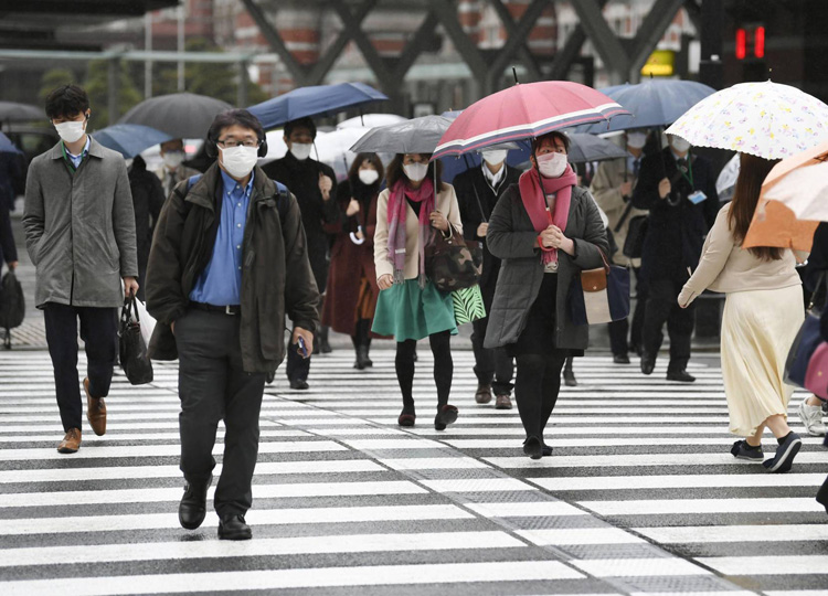 People use a crosswalk near Tokyo Station during the morning commute on April 13.