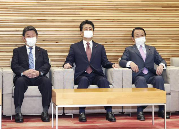 Prime Minister Shinzo Abe (center) and other Cabinet ministers wear face masks before a Cabinet meeting April 3 at the Prime Minister's Office.