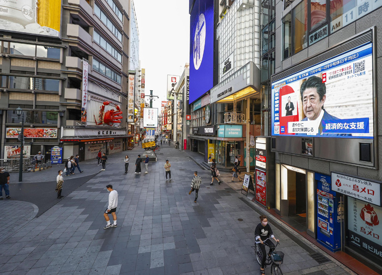 A monitor in Dotonbori, Osaka, shows Prime Minister Shinzo Abe announcing the extension of the nationwide state of emergency on May 4.