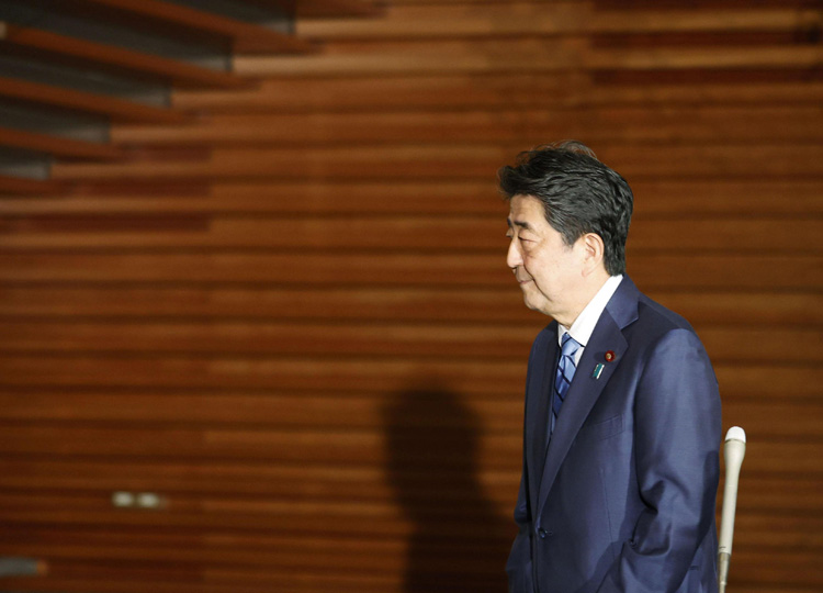 Prime Minister Shinzo Abe walks away after announcing his decision to shelve a controversial prosecutors bill during a briefing with reporters at the Prime Minister's Office on May 18.
