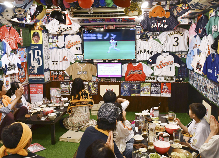 Baseball fans celebrate the start of the coronavirus-delayed season at a pub in Tokyo on June 19.