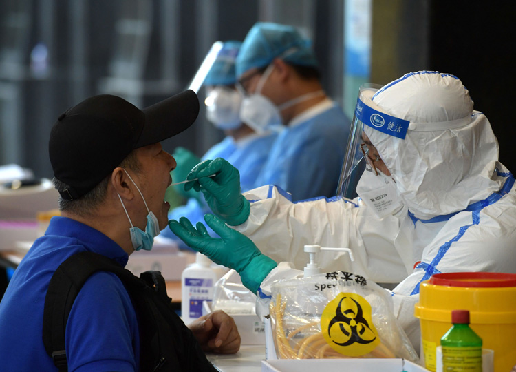 A medical staff in protective suit collects swabs in Nanjing, Jiangsu province, on June 15 from people who have recently traveled to Beijing.