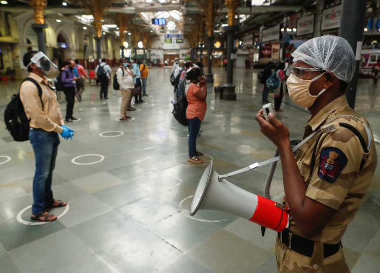 A railway police official makes an announcement on a loudspeaker telling commuters to stand inside the designated circles to maintain social distancing in Mumbai on June 22.