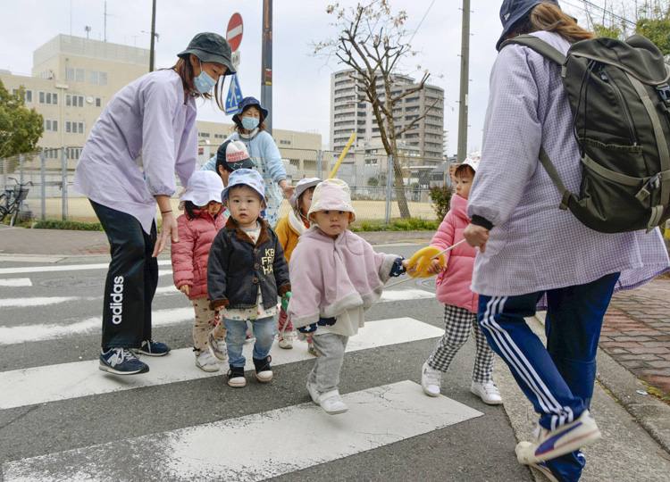 Preschool teachers guide preschoolers across a crosswalk in Osaka in February.
