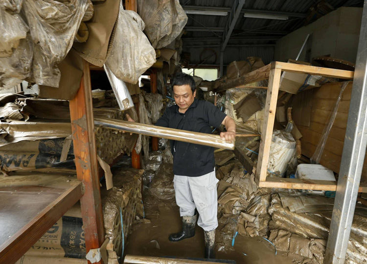 A man cleans his warehouse in Hitoyoshi, Kumamoto Prefecture, on July 7 after torrential rains led to flooding in the area.