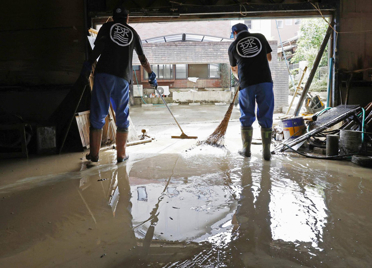 Workers at a tourist raft operator on Kuma River sweep muddy water out of a warehouse July 12 in Hitoyoshi, Kumamoto Prefecture.