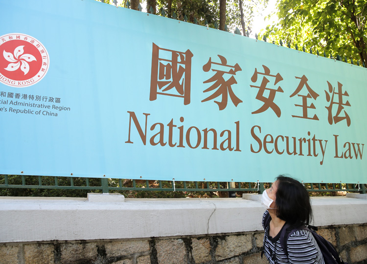 A woman in Hong Kong walks past a promotional banner of the national security law for the city on June 30.