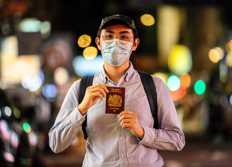 Reese Tan, a 25-year-old tutor, poses with his British National (Overseas) passport on July 3 in Hong Kong.