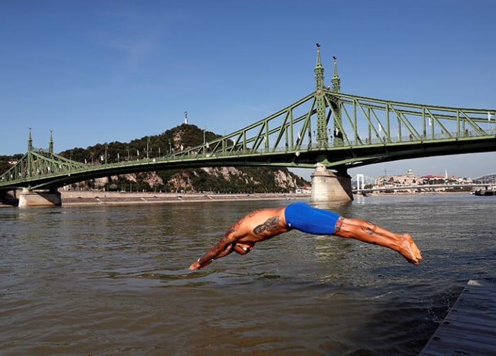 Hundreds brave fast-flowing waters to swim across Danube River in Budapest