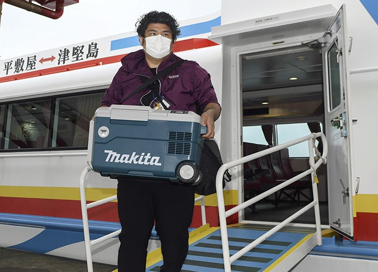 An Uruma City worker carries a case of COVID-19 vaccines after arriving at Tsuken Island, Okinawa Prefecture, on April 15.