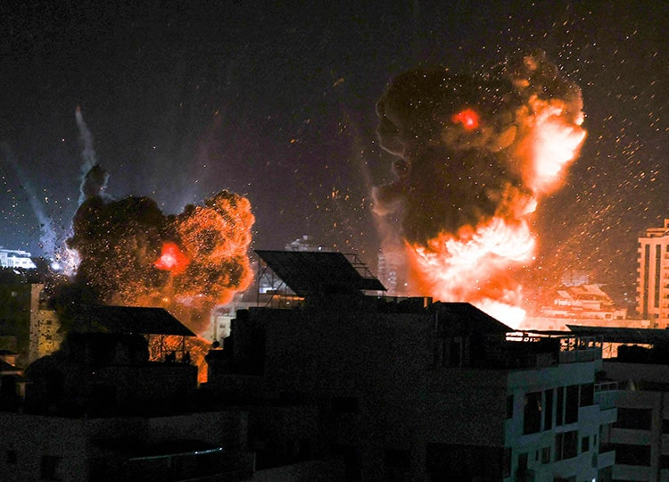 Explosions light up the night sky above buildings in Gaza as Israeli forces shell the Palestinian enclave early on May 18.