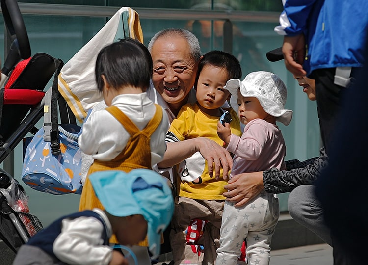 An elderly man plays with children near a commercial office building in Beijing on May 10.