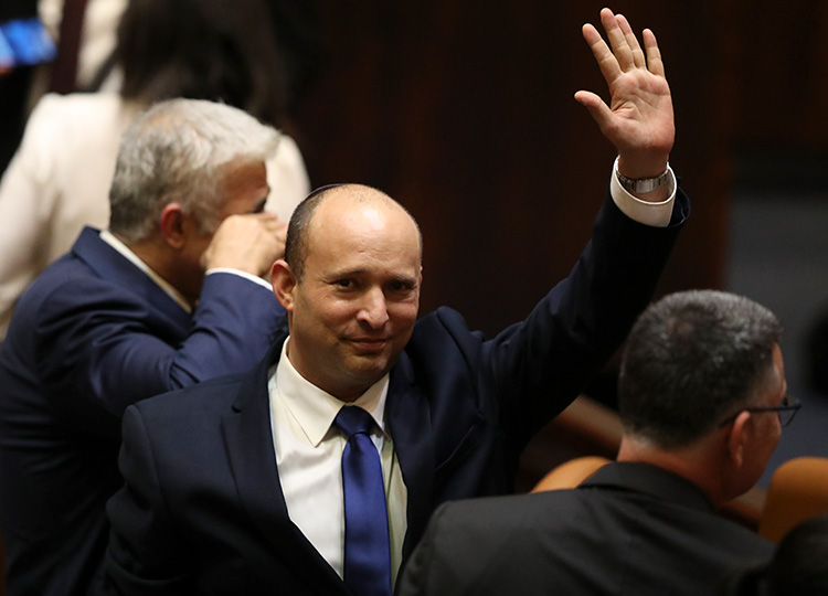 Israel's new prime minister, Naftali Bennett, raises his hand during a session in the Knesset, Israel's parliament, in Jerusalem on June 13.