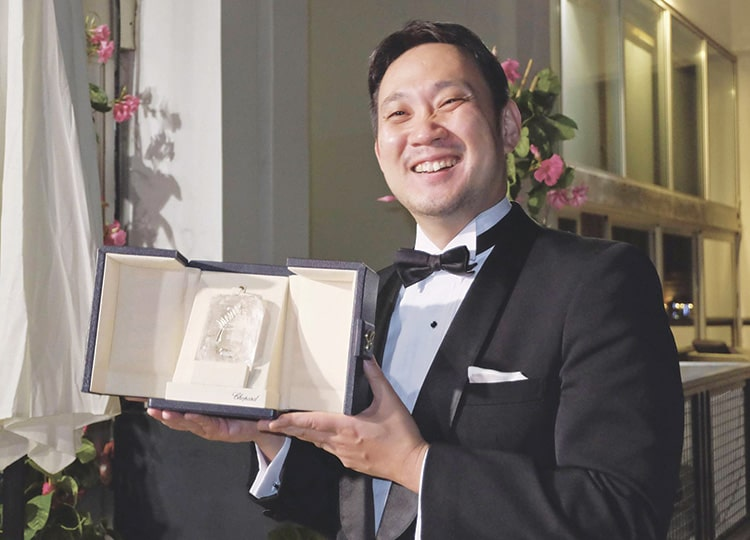 Ryusuke Hamaguchi poses for a photo after winning the best screenplay award at the annual Cannes International Film Festival in France on July 17.