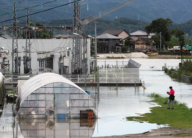 A man looks at a flooded area after heavy rainfall in Tosu, Saga Prefecture, on Aug. 15.