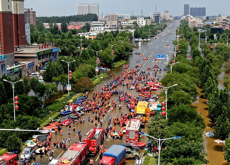 Rescuers evacuate people from a flooded area in Weihui in central China's Henan province on July 26.