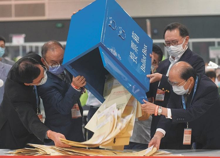 Officials pour out ballots from a box at a counting center in Hong Kong on Sept. 19.