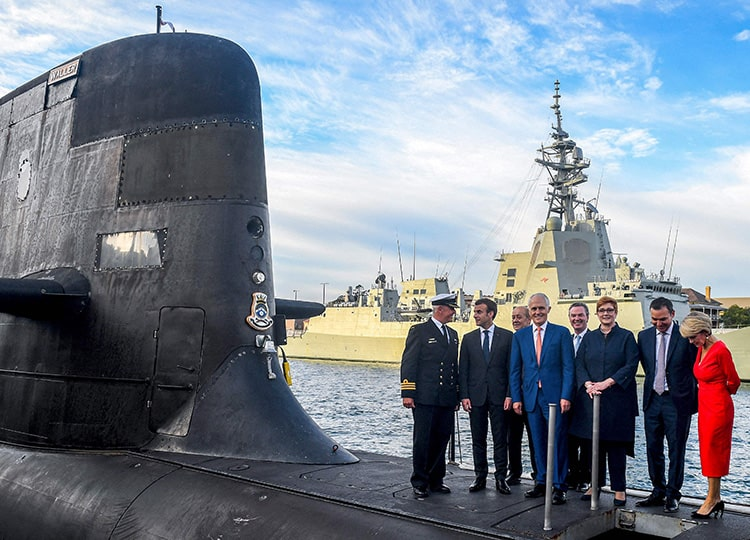 A 2018 file photo shows French President Emmanuel Macron (second from left) and Australian PM Malcolm Turnbull (center) standing on the deck of HMAS Waller submarine in Sydney.
